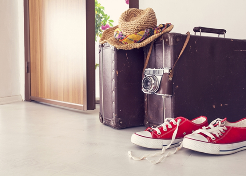 Two black suitcases and a pair of red sneakers on the floor by an open door, with a straw hat and camera resting on the suitcases