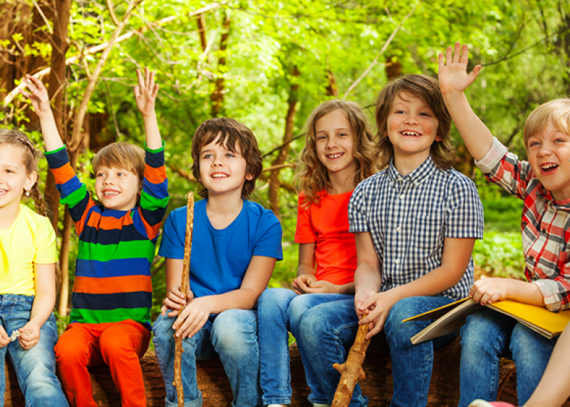 Six young children sitting on a log outdoors, smiling and raising their hands.