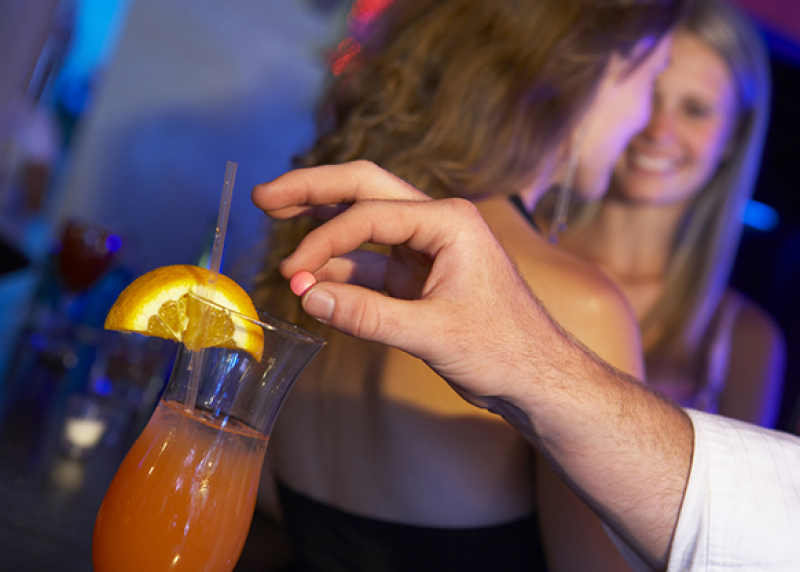 A man's hand preparing to drop a pill in an unattended drink, while two women talk in the background.