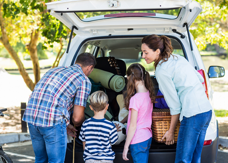 Parents and two children packing the back of an SUV for a trip.