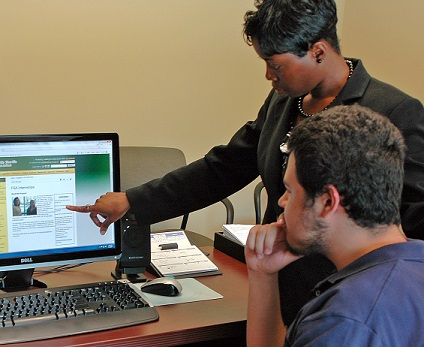 Tanesha Williams pointing to a computer screen at the FSA website, while a seated male intern looks at the screen