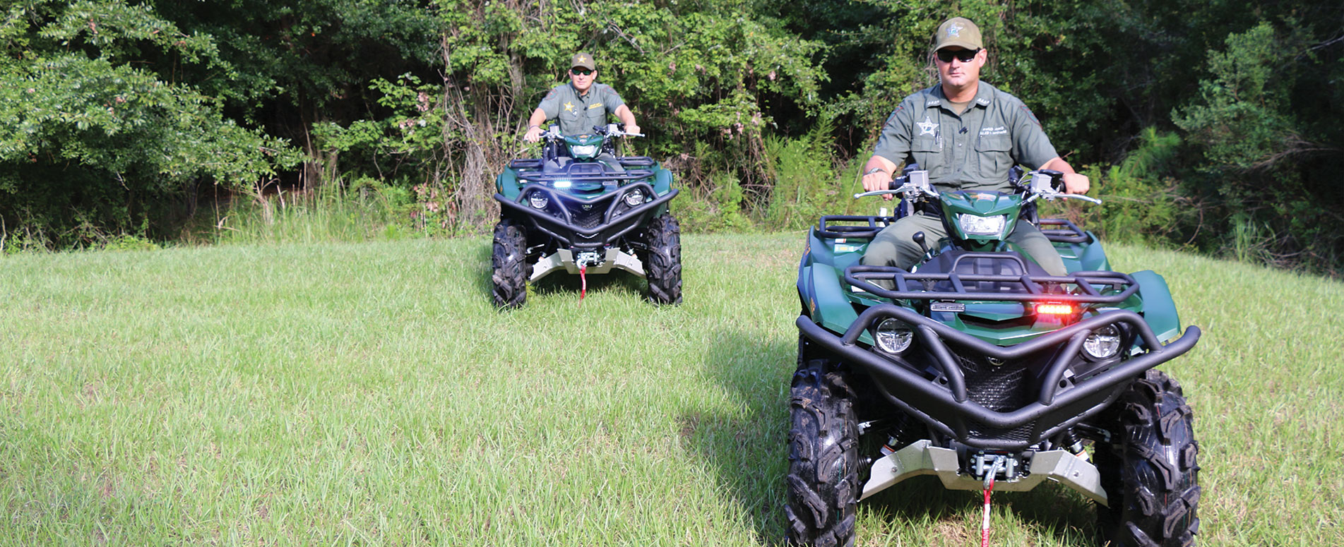 Two male deputies driving ATVs through the grass, toward the camera