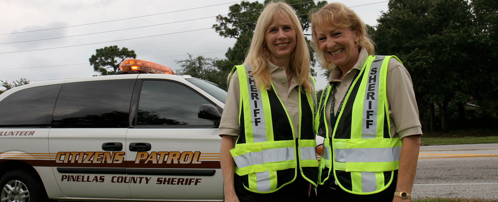 Two women in Sheriff caution vests, standing in front of a white van with the word Volunteer on the side