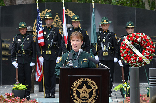 Alachua County Sheriff Sadie Darnell standing at a podium and addressing the crowd at the FSA Memorial